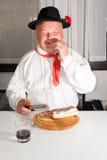 Man wearing traditional clothing enjoying bacon Stock Photo