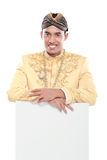 Man wearing traditional dress of java holding blank board Stock Photography