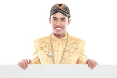 Man wearing traditional dress of java holding blank board Royalty Free Stock Image