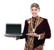 Man wearing traditional dress of java holding laptop Royalty Free Stock Photo