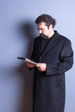 Man Wearing Trench Coat Reading from Tablet. Three Quarter Length of Man with Beard and Curly Hair Wearing Long Dark Trench Coat and Looking Down Seriously at Stock Photography