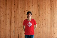 Man wearing Tunisia flag color and standing with crossed behind the back hands on the wooden wall background. Red field with white sun-disc containing a red royalty free stock image