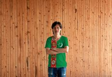 Man wearing Turkmenistan flag color shirt and cross one`s arm on wooden wall background. Green field with red stripe containing five carpet guls, crescent and royalty free stock image