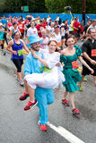 Man Wearing Tux Carries Fiancee Across 10K Race Finish Line. Atlanta, GA, USA - July 4, 2015: A young man dressed in a groom's tuxedo, carries his fiancee in a stock image