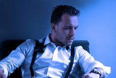 Man wearing tuxedo in hotel room, sitting in chair with loose tie royalty free stock photos