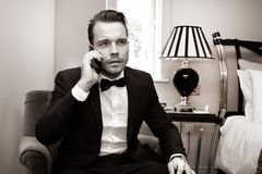 Man wearing tuxedo in hotel room talking on mobile phone, cellphone Stock Image