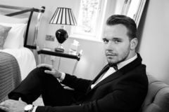Man wearing tuxedo in hotel room talking on mobile phone, cellphone stock photos