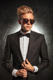 Man wearing tuxedo pose in studio while fixing his jacket Royalty Free Stock Photography