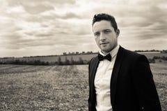 Man wearing tuxedo walks through field in countryside royalty free stock image