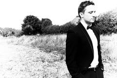 Man wearing tuxedo walks through field in countryside stock photo