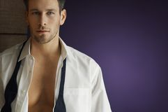 Man Wearing Unbuttoned Shirt. Portrait of a smart man wearing unbuttoned shirt over purple background Stock Photos