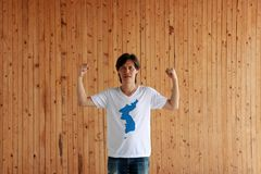 Man wearing Unification Korea flag color of shirt and standing with raised both fist on the wooden wall background royalty free stock image