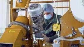 Man wearing uniform cleans details of machine. Worker cleans the machine for making tea. He`s using vacuum cleaner and cleans the equipment from dust and dirty stock footage