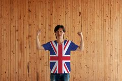 Man wearing union jack flag color of shirt and standing with raised both fist. On the wooden wall background royalty free stock photography
