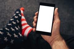Man wearing usa flag socks using mobile phone Royalty Free Stock Photography