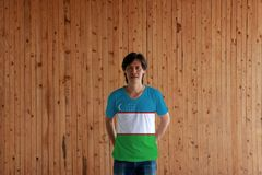 Man wearing Uzbekistan flag color of shirt and standing with crossed behind the back hands on the wooden wall background. Blue white and green stripes with two stock images