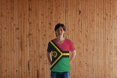 Man wearing Vanuatu flag color of shirt and standing with crossed behind the back hands on the wooden wall background. Red and green with black and yellow royalty free stock images