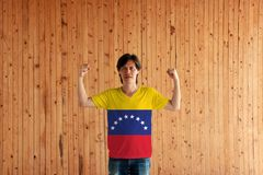 Man wearing Venezuela flag color of shirt and standing with raised both fist on the wooden wall background. Yellow blue and red with an arc of eight white royalty free stock image
