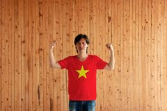 Man wearing Vietnam flag color of shirt and standing with raised both fist on the wooden wall background. Yellow star on red color royalty free stock image