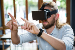 Man wearing virtual glasses in coffee shop. Young man wearing virtual glasses in coffee shop Royalty Free Stock Photography