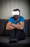 Man wearing virtual reality 3D glasses. Man wearing virtual reality 3D glasses watches a scary movie alone Stock Images