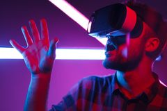 Man wearing virtual reality glasses. Crop view of male wearing virtual reality glasses shocked raising hand with mouth opened indoors Stock Photos