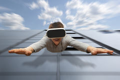 Man wearing virtual reality glasses flying from a skyscraper. Young man wearing virtual reality glasses flying from a skyscraper stock images