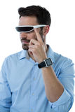 Man wearing virtual reality glasses and smart watch. Against white background Royalty Free Stock Images