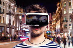 Man wearing virtual reality goggles against night city Stock Image