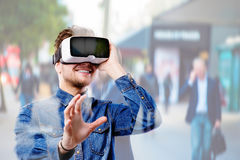 Man wearing virtual reality goggles. Crowded street of London. Stock Image