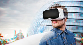 Man wearing virtual reality goggles. London, England. Hipster man in denim shirt wearing virtual reality goggles. London, England stock photo