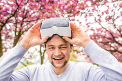 Man wearing virtual reality goggles outside in spring nature Royalty Free Stock Photos