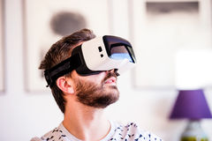 Man wearing virtual reality goggles, sitting in living room Stock Photos