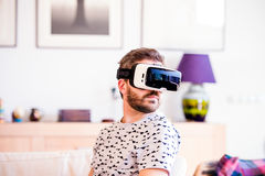 Man wearing virtual reality goggles, sitting in living room Stock Image