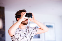 Man wearing virtual reality goggles, standing in living room Stock Photography