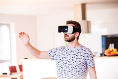 Man wearing virtual reality goggles, standing in living room Royalty Free Stock Images