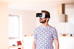 Man wearing virtual reality goggles, standing in living room Royalty Free Stock Photography