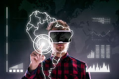 Man wearing virtual reality goggles. Studio shot, black backgrou. Hipster man in checked shirt wearing virtual reality goggles, reaching out. Studio shot on royalty free stock images