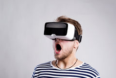 Man wearing virtual reality goggles. Studio shot, black backgrou. Hipster man in striped black and white sweatshirt wearing virtual reality goggles. Studio shot stock photos