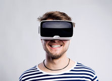 Man wearing virtual reality goggles. Studio shot, gray backgroun Royalty Free Stock Photography