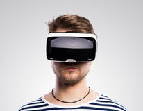 Man wearing virtual reality goggles. Studio shot, gray backgroun Stock Image