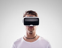 Man wearing virtual reality goggles. Studio shot, gray backgroun Royalty Free Stock Photo