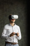 Man wearing virtual reality goggles watching movies or playing video games. The vr headset design is generic and no logos Royalty Free Stock Images