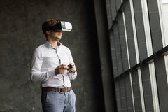 Man wearing virtual reality goggles watching movies or playing video games. The vr headset design is generic and no logos. The VR headset design is generic and Royalty Free Stock Images