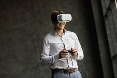 Man wearing virtual reality goggles watching movies or playing video games. The vr headset design is generic and no logos. The VR headset design is generic and Royalty Free Stock Photography