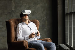 Man wearing virtual reality goggles watching movies or playing video games. The vr headset design is generic and no logos Stock Images