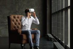 Man wearing virtual reality goggles watching movies or playing video games. The vr headset design is generic and no logos Royalty Free Stock Photography