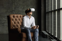 Man wearing virtual reality goggles watching movies or playing video games. The vr headset design is generic and no logos Royalty Free Stock Image