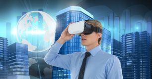 Man wearing virtual reality headset with Tall buildings with world globe. Digital composite of Man wearing virtual reality headset with Tall buildings with world Royalty Free Stock Image