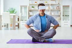 The man wearing virtual reality vr glasses doing sports at home. Man wearing virtual reality VR glasses doing sports at home Stock Images